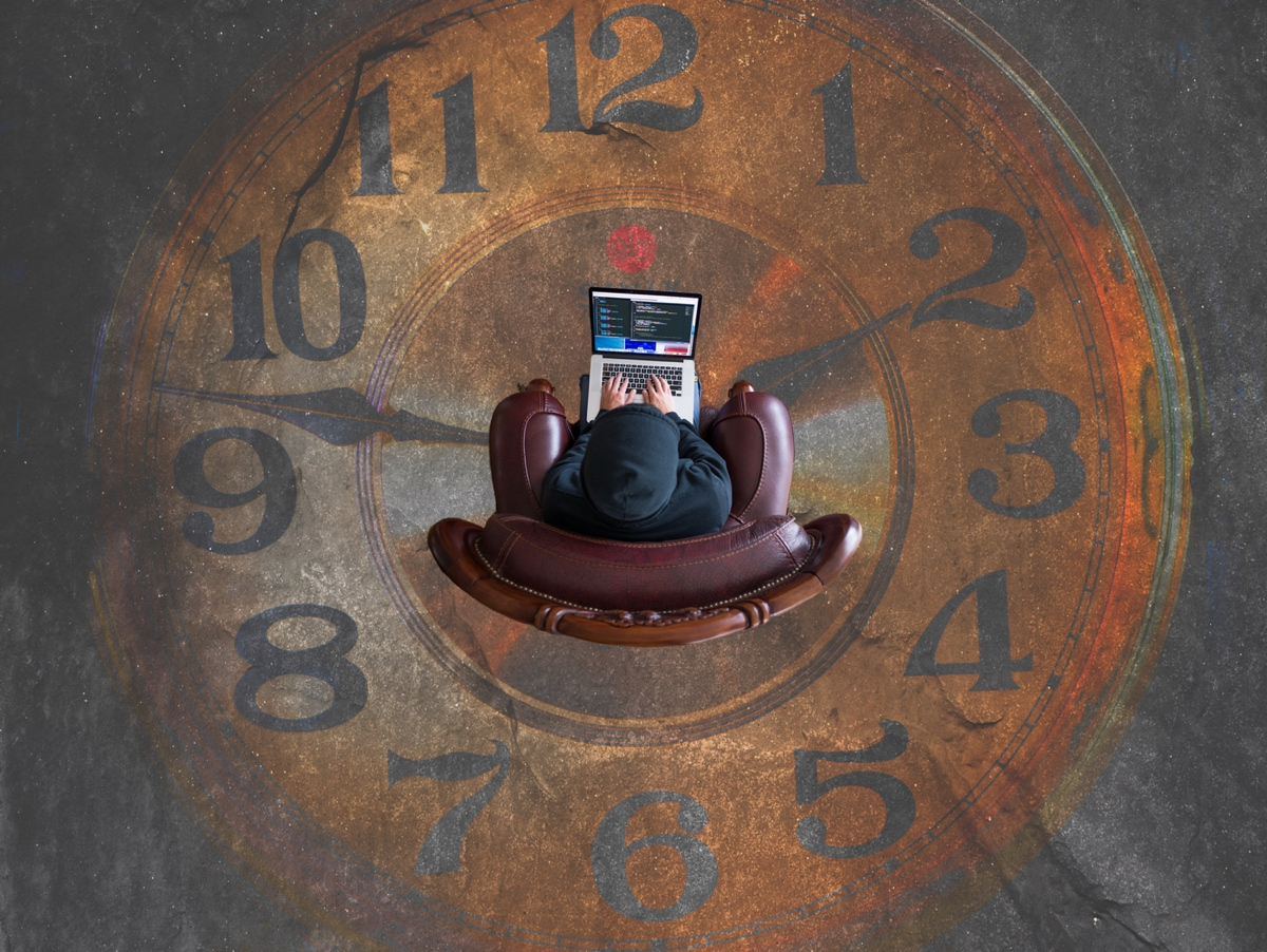 Clock with person sitting in the middle in an armchair on laptop