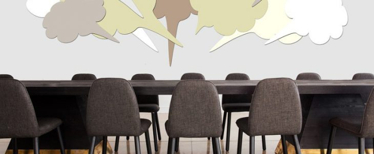 Conference table with speech bubbles above the center.