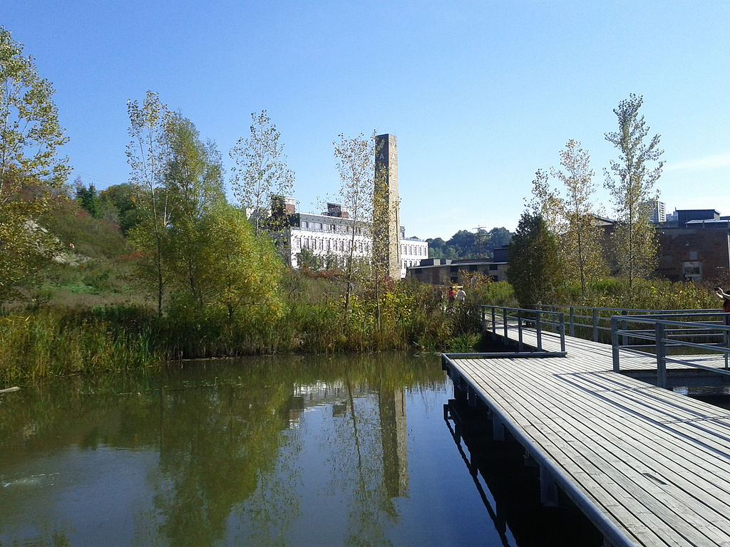 View of the Don Valley Brickworks with pond and wood dock in foreground.