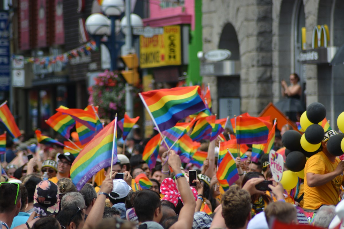 Pride rainbow flags wave in the crowd.