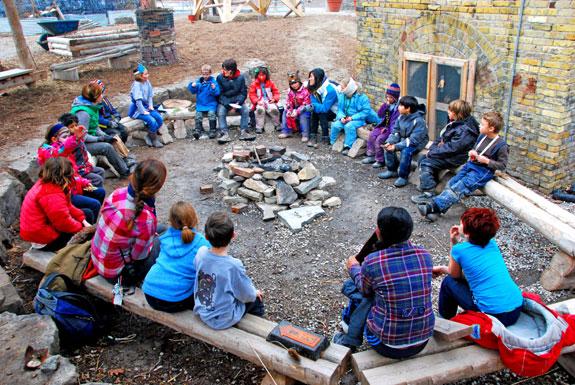 Kids circle around the campfire at Evergreen Brick Works.