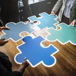 Four people hold together four large green and blue jigsaw puzzle pieces.