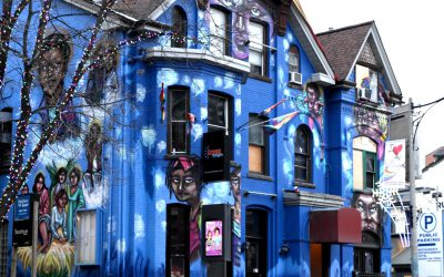 Building with a bright blue mural depicting the history of drag in Toronto.